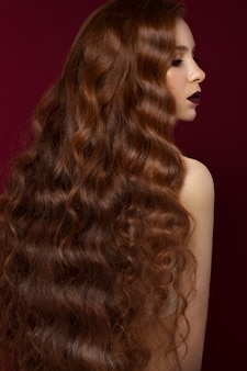 Hermosa pelirroja con un cabello perfectamente rizado y maquillaje clásico. cara de belleza