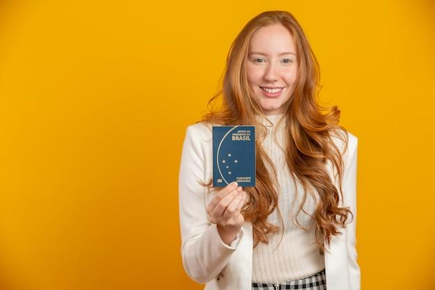 Hermosa pelirroja chica de pelo rizado en viajes. próximo viaje. chica sujetando el pasaporte brasileño. en amarillo
