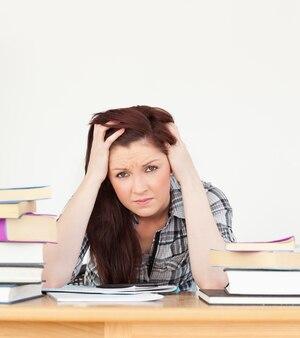 Hermosa pelirroja deprimida mientras estudiaba para un examen