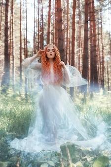 Hermosa pelirroja mujer ninfa del bosque en vestido azul