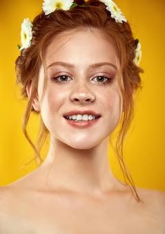 Hermosa pelirroja positiva con una corona de manzanilla en la cabeza
