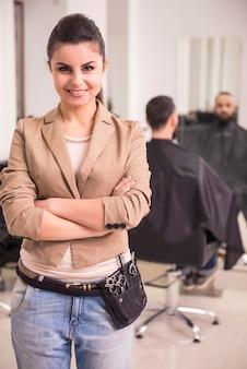 Hermosa peluquera en cinturón de cuero con herramientas en el salón.