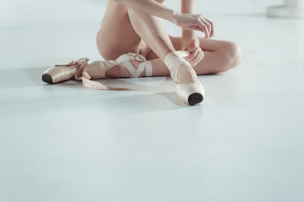Hermosa y pequeña bailarina poniéndose los zapatos de punta