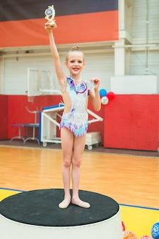 Hermosa y pequeña gimnasta entrenando en la alfombra y lista para competiciones