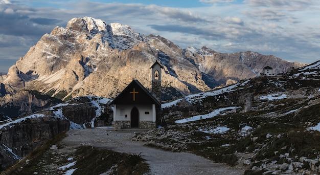 Hermosa pequeña iglesia en los nevados alpes italianos en invierno