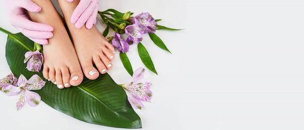 Hermosa piel femenina perfecta piernas pies vista superior con flores tropicales y hoja de palma verde
