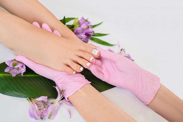 Hermosa piel perfecta piernas femeninas pies vista superior con flores tropicales y hojas de palma verde