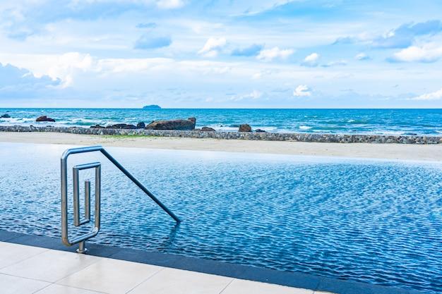 Hermosa piscina al aire libre en el complejo hotelero con nubes blancas y cielo azul para relajarse