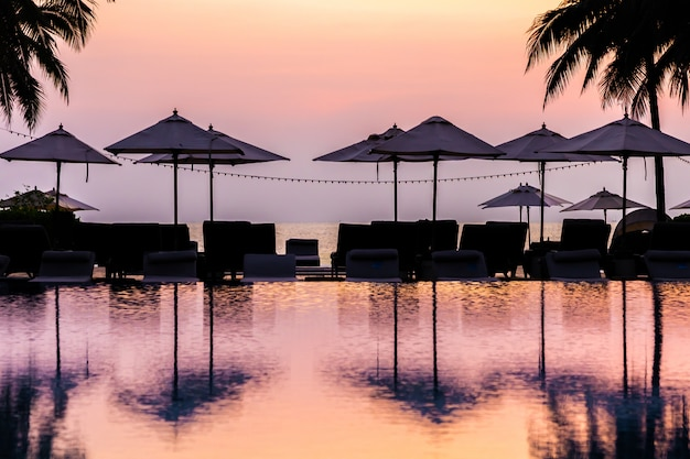 Hermosa piscina al aire libre con silla de sombrilla de silueta alrededor en el resort al amanecer