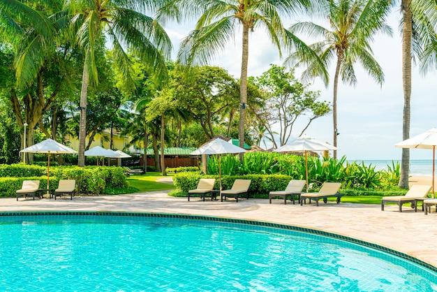 Hermosa piscina tropical en el complejo hotelero con hamacas y sombrillas