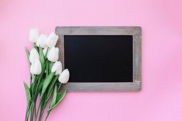 Hermosa pizarra para maqueta con bonitos tulipanes sobre fondo rosa