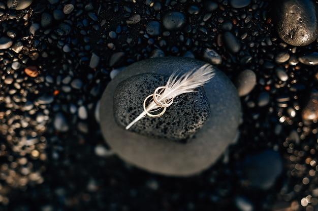 Hermosa plata con anillos de boda y plumas