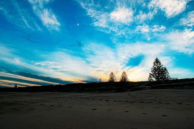 Hermosa playa de arena bajo un cielo nublado azul al amanecer.