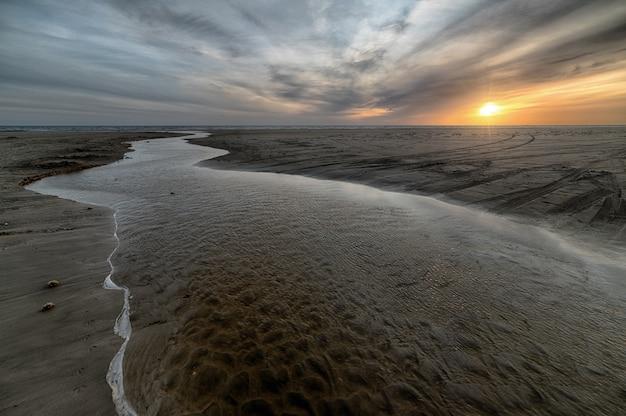 Hermosa playa de arena con mar durante la marea baja.