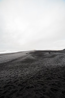 Hermosa playa de arena negra volcánica en dyrholaey, islandia.