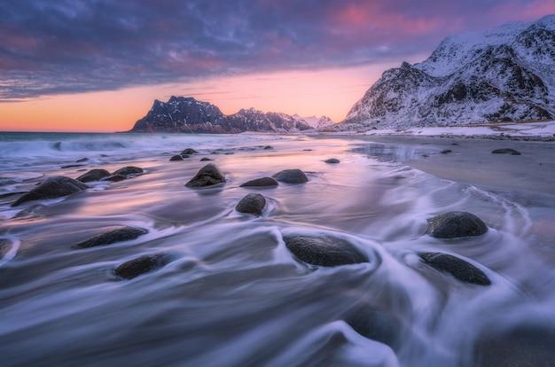 Hermosa playa de arena con piedras en agua borrosa, colorido cielo rosa nublado y montañas nevadas al atardecer
