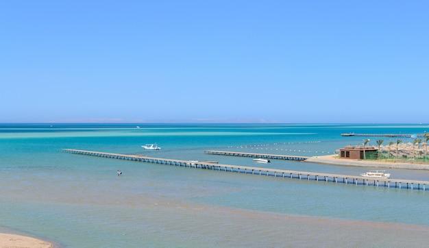 Hermosa playa paradisíaca del mar azul con un muelle y un panorama de yates