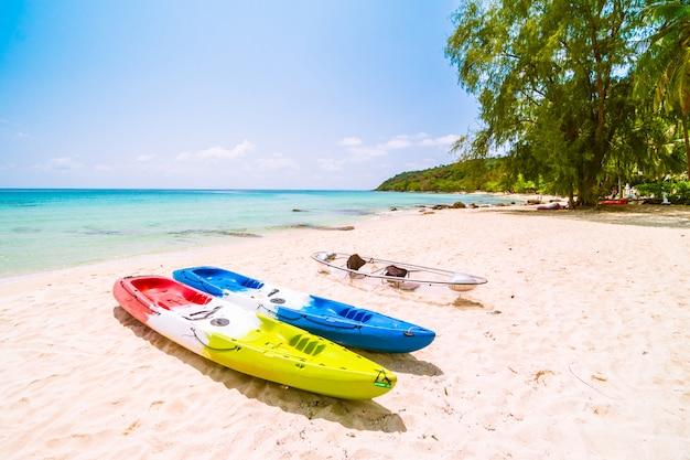 Hermosa playa paradisíaca y mar con kayak en bote.