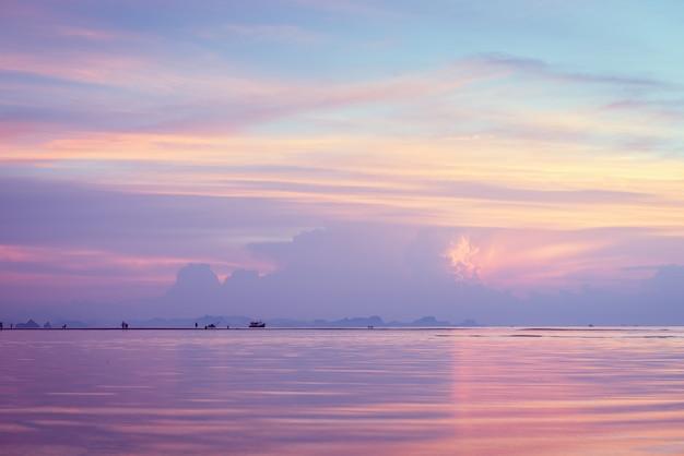 Hermosa playa puesta de sol con grandes nubes de lluvia y cielo dorado claro