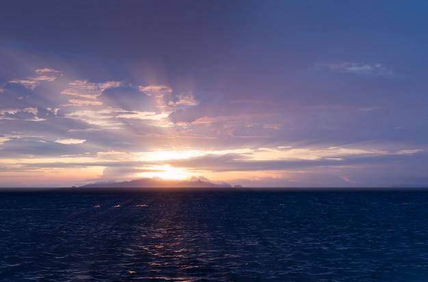 Hermosa playa puesta de sol con grandes nubes de lluvia y cielo de luz dorada