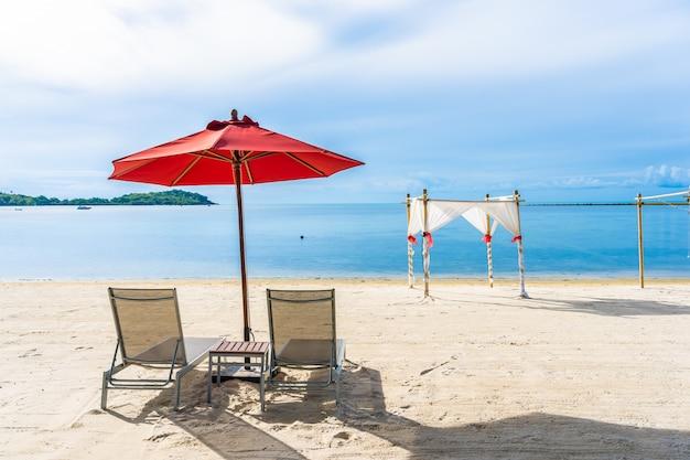 Hermosa playa tropical al aire libre mar océano con silla sombrilla y lounge deck alrededor de allí en el cielo azul nube blanca