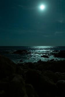 Hermosa playa tropical con luna llena en cielos nocturnos