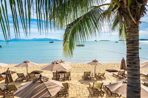 Hermosa playa tropical mar y océano con palmera de coco y sombrilla y silla en cielo azul y nube blanca