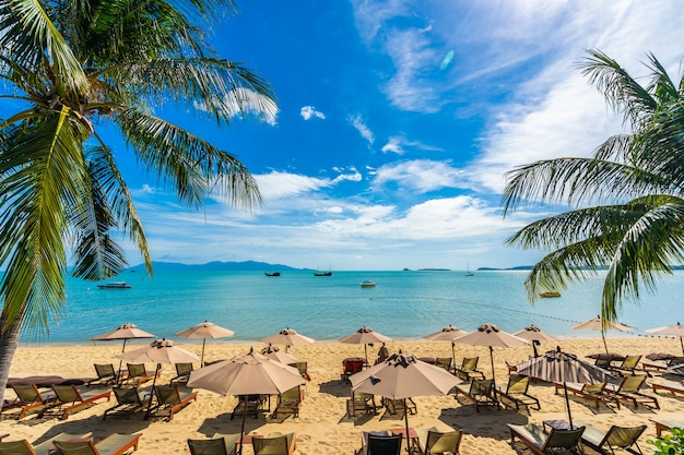 Hermosa playa tropical mar y océano con palmera de coco y sombrilla y silla en cielo azul