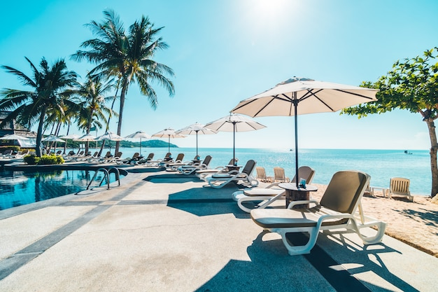 Hermosa playa tropical y mar con sombrilla y silla alrededor de la piscina.