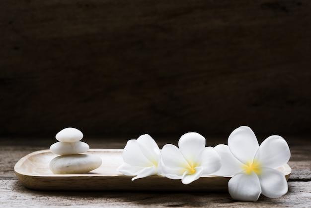 Hermosa plumeria o templo, flor de spa con piedras blancas zen en bandeja de madera sobre fondo de madera rústica