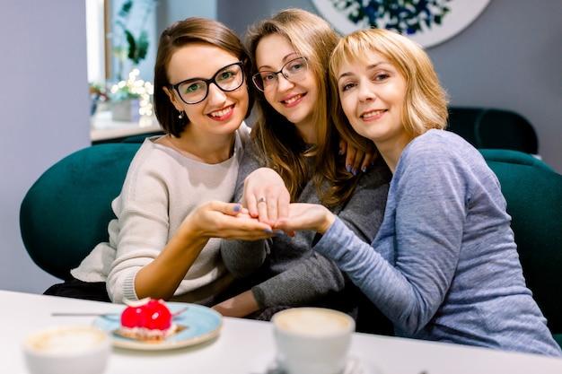 Hermosa prometida bonita mujer feliz posando para una foto mientras muestra su anillo de compromiso junto con sus dos amigas en el café en el interior