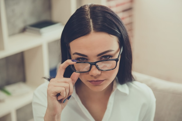 Hermosa psicóloga toca sus lentes.