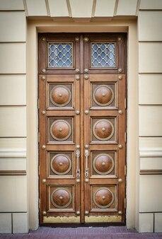Hermosa puerta grande de madera marrón con manijas talladas