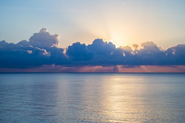 Hermosa puesta de sol y camino de plata en el mar, nubes azules en el cielo, fondo
