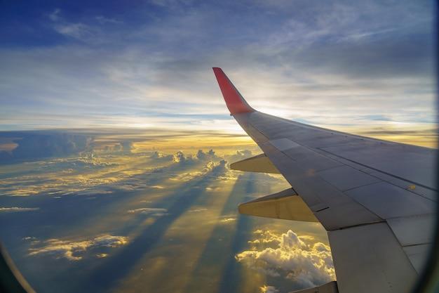 Hermosa puesta de sol, cielo en la vista superior, avión volando vista desde dentro de la ventana de aviones de viajar.