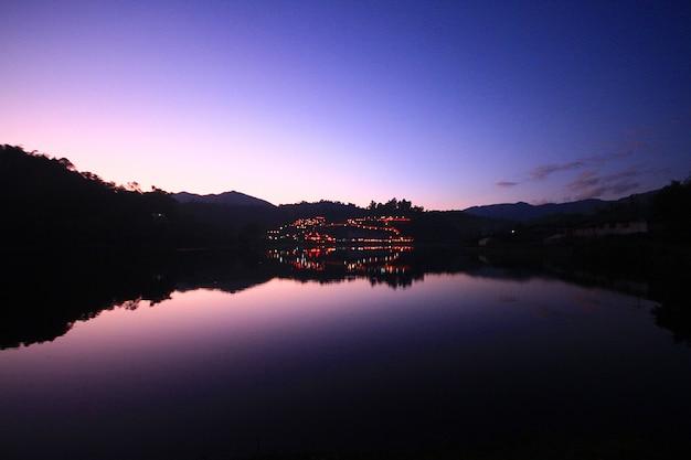 Hermosa puesta de sol y crepúsculo de la reflexión del cielo sobre la superficie del agua y el lago en la aldea de la tribu hill en tailandia