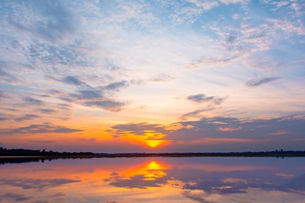 Hermosa puesta de sol detrás de las nubes y el cielo azul sobre la laguna