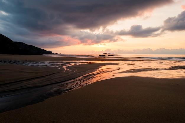 Hermosa puesta de sol dorada de verano sobre el mar negro y reflejo en la playa