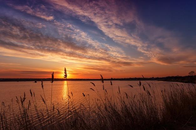 Hermosa puesta de sol en el lago con nubes y reflejos en el agua