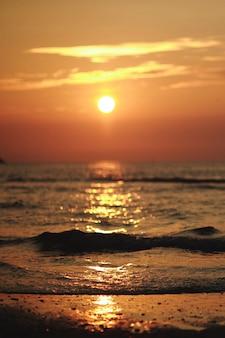 Hermosa puesta de sol naranja brillante en la playa