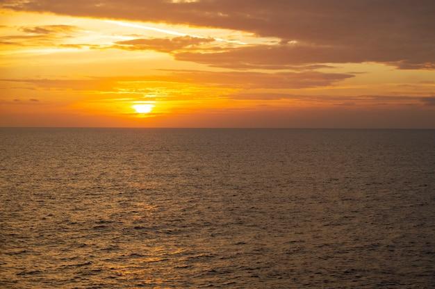 Hermosa puesta de sol naranja colorido en el mar con nubes oscuras y sol brillante. concepto de viaje, cruceros por el mar