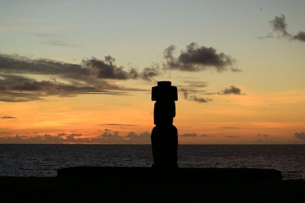 Hermosa puesta de sol en el océano pacífico con la silueta de moai en ahu tahai, isla de pascua, chile