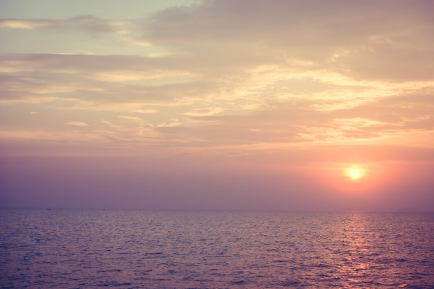 Hermosa puesta de sol en la playa y el mar