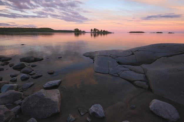 Hermosa puesta de sol rosa en el lago ladoga en karelia, rusia en el parque nacional ladoga skerries en verano. paisaje natural con rocas de agua, islas de piedra y bosque cerca de la costa