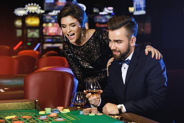 Hermosa y rica pareja jugando a la ruleta en el casino