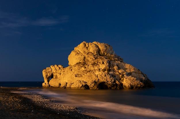 Hermosa roca en el agua por la noche