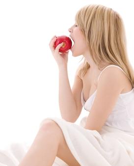 Hermosa rubia brillante con manzana roja