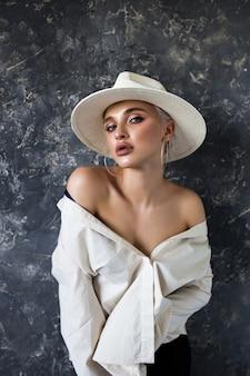 Hermosa rubia en una camisa blanca con pantalón negro y un sombrero blanco sobre un azul.