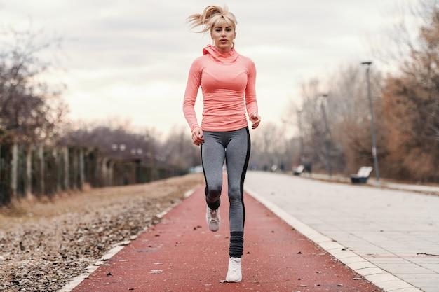 Hermosa rubia caucásica dedicada en ropa deportiva y con cola de caballo corriendo en la pista de carreras.