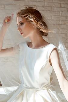Hermosa rubia delgada en el sol de la tarde con un vestido blanco largo. retrato